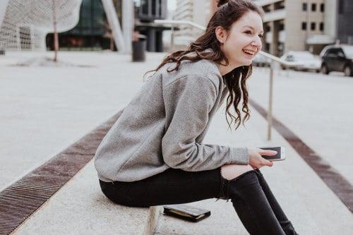 Młoda kobieta siedzi na schodach z telefonem komórkowym w dłoni