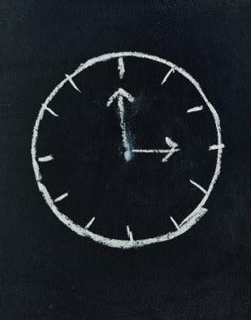 Narysowany kredą na tablicy zegar