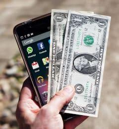 Mężczyzna trzyma w dłoni dolary i telefon komórkowy